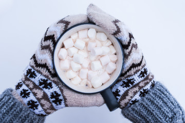 hands of the girl holding a mug with hot chocolate on the background of snow