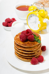 stack of pancakes with fresh raspberries for breakfast on white table, top view