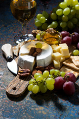 snacks, wine and camembert on a dark background, vertical
