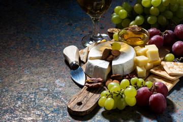 snacks, wine and camembert and dark background