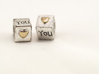 Silver cubes on a white background with a confession of love on St. Valentine's Day