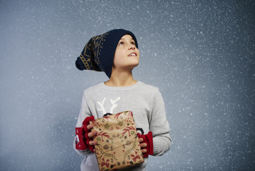 Boy with gift box looking at snow .
