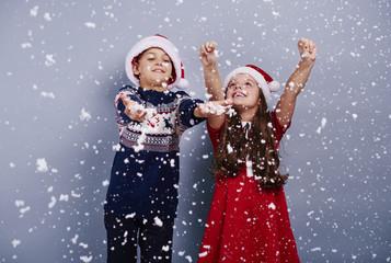 Happy children catching snowflake.