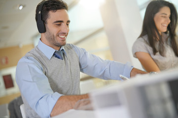 Businessman in office using headset in front of laptop