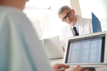 Mature doctor in office working on laptop computer