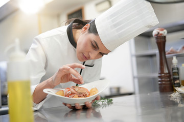 Closeup of cook chef in professional kitchen preparing dish