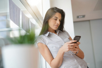 Businesswoman in office relaxing, using smartphone