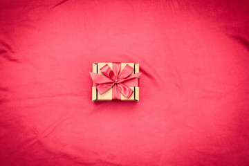 One gift box tied with satin coloured ribbon on a red background a Red heart.
