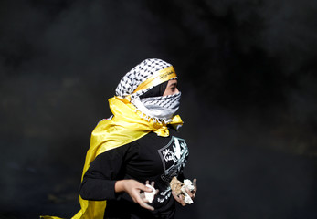 Palestinian girl holds stones before being wounded during clashes with Israeli troops at a protest near the Jewish settlement of Beit El, near the West Bank city of Ramallah