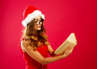 Young attractive Santa girl in red dress over red background
