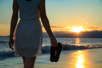 Young, sexy woman is walking at a beautiful sunset beach. holding her flip flops in her hand. sexy short dress skirt. wet feet legs. sundown mountains