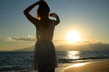 Young, sexy woman is walking at a beautiful sunset beach. holding her flip flops in her hand. sexy short dress skirt. wet feet legs. sundown mountains