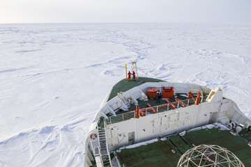 polar icebreaker navigating through thick ice floe