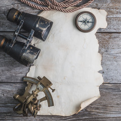 vintage card with compass and others measurement instruments on the wooden timber