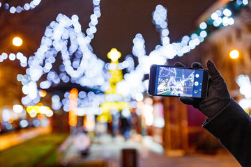 Woman Taking photo of European Christmas Market with light bulbs on Smartphone at night
