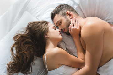 top view of young couple cuddling in bed in morning