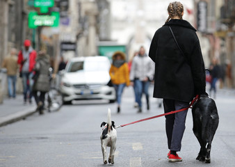 A woman walks with her dogs in downtown Rome