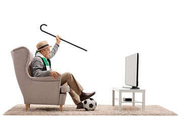 Overjoyed elderly soccer fan with a scarf and cane watching television