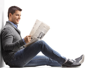 Young man seated on the floor reading a newspaper and leaning against a wall