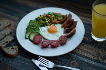 English breakfast. Fried eggs, sausages, avocado, beans, toasts, tomatoes, orange juice on wooden table. Top view with copy spac