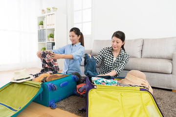 young girlfriends packing clothes put in suitcase