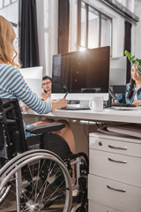cropped image of woman in wheelchair using graphics tablet at modern office
