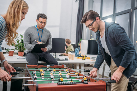 young man and woman playing in table soccer at modern office