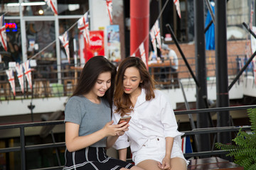 Asia girl and friend ethnic German-Thai taking smart phone selfie in department store.