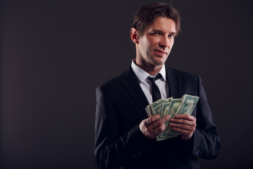 Photo of man in suit counting dollars
