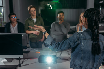 young people watching presentation in modern office, woman pointing on screen