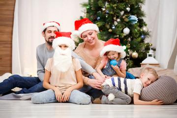 Photo of happy family in Santa caps at Christmas tree