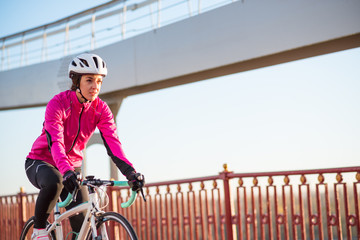Young Woman in Pink Jacket Riding Road Bicycle on the Bridge Bike Line in the Cold Sunny Autumn Day. Healthy Lifestyle.