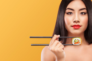 Closeup portrait of asian woman eating sushi and rolls on a yellow background. Copyspace.