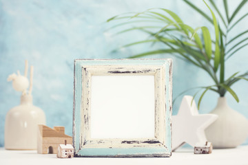 Bright tropical mock up with vintage white and blue photo frame, palm leaves in vase and home decor against blue wall. Travel, summer concept