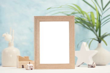 Bright tropical mock up with beige photo frame, palm leaves in vase and home decor on blue background. Travel, summer concept