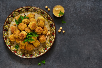 Arabian dish - falafel with sauce and cilantro on a black background.