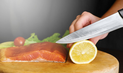 a piece of red fish on a wooden board, knife lies on the table near the fish, on a black background