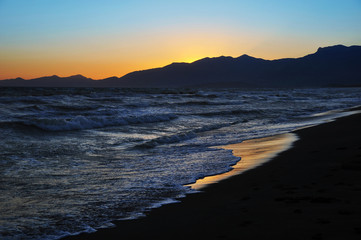 Beautiful sunset on the beach with mountains in the background
