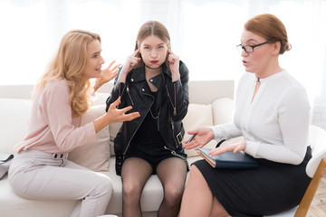 A girl in a leather jacket does not want to listen to adults at a psychologist's reception.