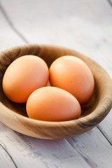 eggs in a wooden bowl on the table from the old boards close up