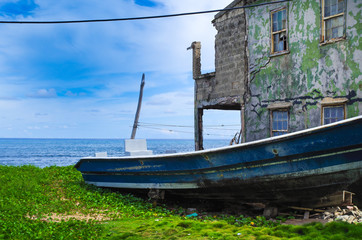 Outdoor view of a destroyed boat and old house in the shore of the beach in a sunny day in San Andres, Colombia