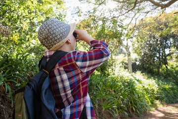 Boy looking through binoculars in the forest