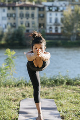 Young Japanese woman practicing yoga exercises near a river in a summer day in the city