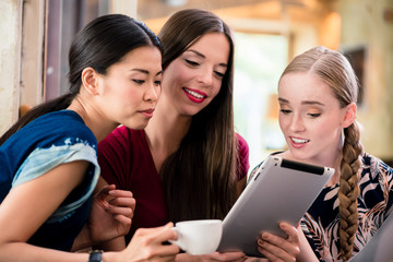 Three chatty young women looking at pictures on tablet computer indoors
