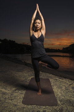 Young woman practicing yoga near riverbank during sunset