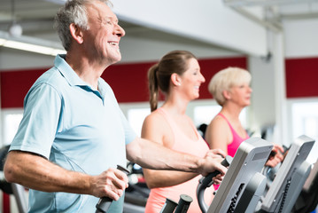 Happy seniors train on cross trainer with personal trainer at the gym