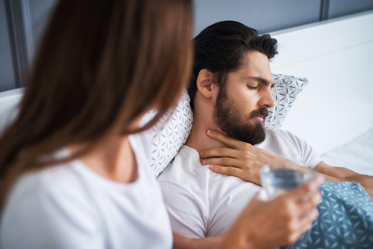 Close up of attractive handsome bearded man having throat pain and lying in the bed at home while his careful girlfriend or wife sitting next to him with a glass of water.