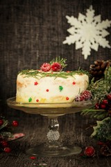 Homemade Christmas cake with frosting on festive Xmas backgrounfd, selective focus