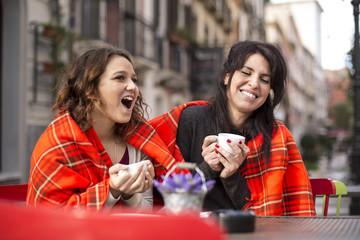 2 amiche in un bar all'aperto si fanno belle risate bevendo un te sotto un plaid colorato.