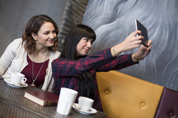 Ragazze in un bar si fanno un selfie con un tablet divertite facendo un bel sorriso